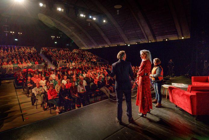 Hoofdredacteur Lucas van Houtert in gesprek met presentator Anne-Marie Fokkens. Ook op het podium: krantenbezorger Ingrid Kuijk.