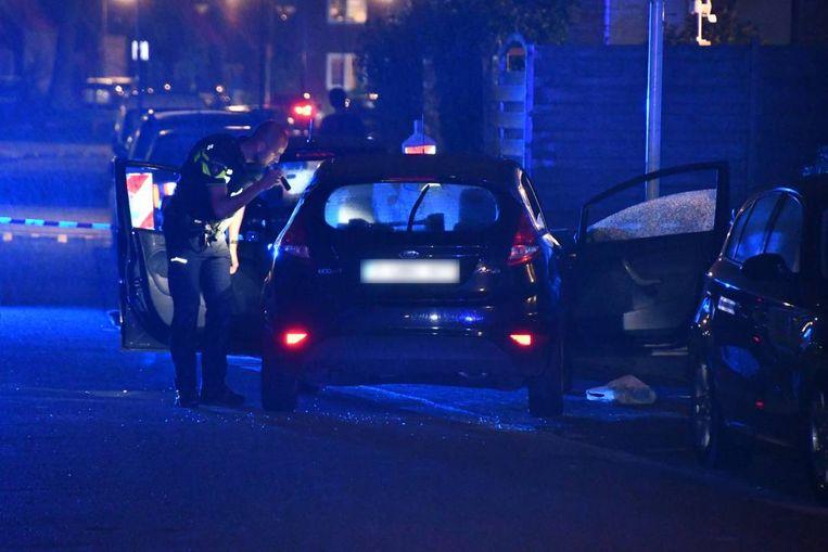 Politie bij de beschoten auto.