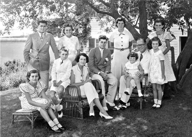 De Kennedy's in Hyannis Port in 1934. Zittend, van links naar rechts: Pat, Bobby, Rose, Jack en Joe met Teddy op schoot. Staand: Joe Junior, Kick, Rosemary, Eunice en voor haar Jean. Beeld Uitgeverij Unieboek / Het Spectrum