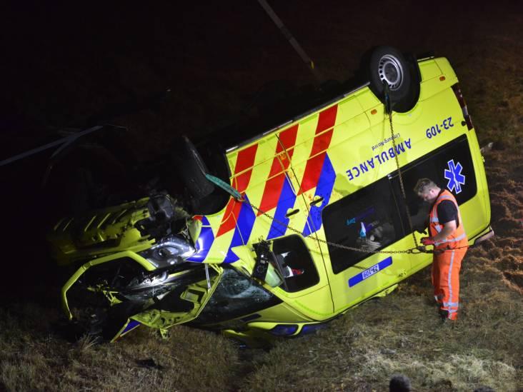 Ambulance ramt verkeersbord en belandt op zijn kop in sloot langs A2