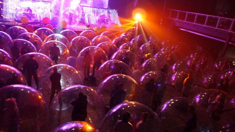 De Amerikaanse band Flaming Lips geeft een vrij letterlijke invulling aan het begrip 'sociale bubbel' tijdens een coronaproof concert in Oklahoma City. Beeld REUTERS