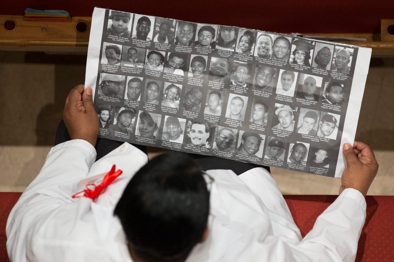Een vrouw bekijkt een lijst van personen die naar verluidt door politiegeweld zijn omgekomen. Beeld EPA