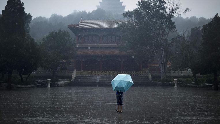 Een Chinese jongen in de regen. Beeld afp