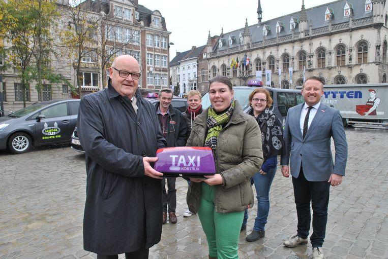 Schepen Rudolf Scherpereel geeft het nieuwe licht aan Delphine Hanssens. Op de achtergrond: twee chauffeurs van het bedrijf van Hanssens, Ellie Samyn van de dienst Economie en schepen Axel Weydts.
