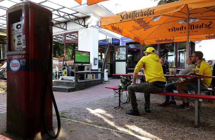 Borussia-fans volgen de wedstrijd op het terras van een café.