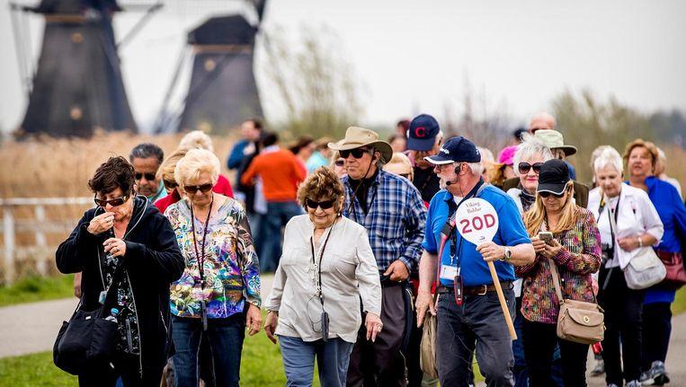 Een groep toeristen bij de molens op Kinderdijk Beeld anp