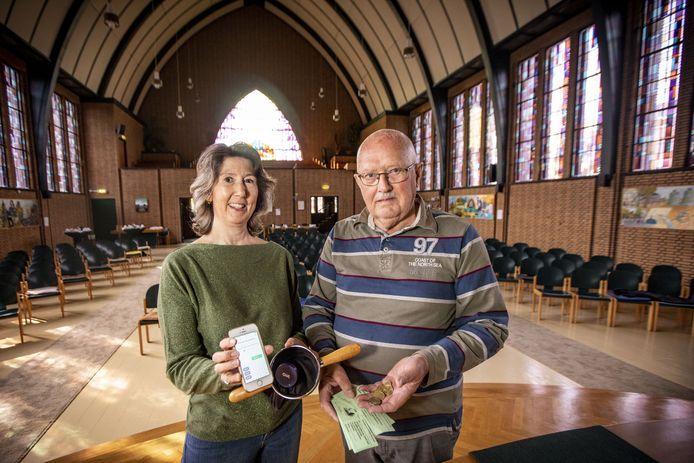 Initiatiefnemer Hanneke Bugter en Anton Scholten, verkoper van collectebonnen, tonen de betaalmogelijkheden in de collectezak in de Hofkerk