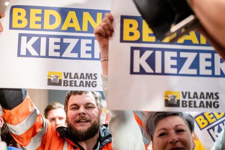Mensen houden voor het Vlaams Belang borden omhoog met daarop de tekst 'Bedankt Kiezers'. Beeld BELGA