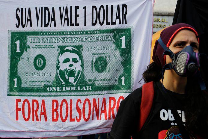"""""""Uw leven is een dollar waard. Oprotten Bolsonaro!"""" staat op een van de spandoeken die de demonstranten meedroegen."""