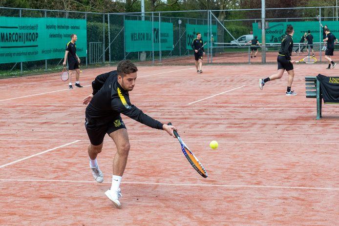 De voetballers van SV Meerkerk, met Daan Verhoeven in volle actie vooraan, leven zich uit op de tennisbaan.