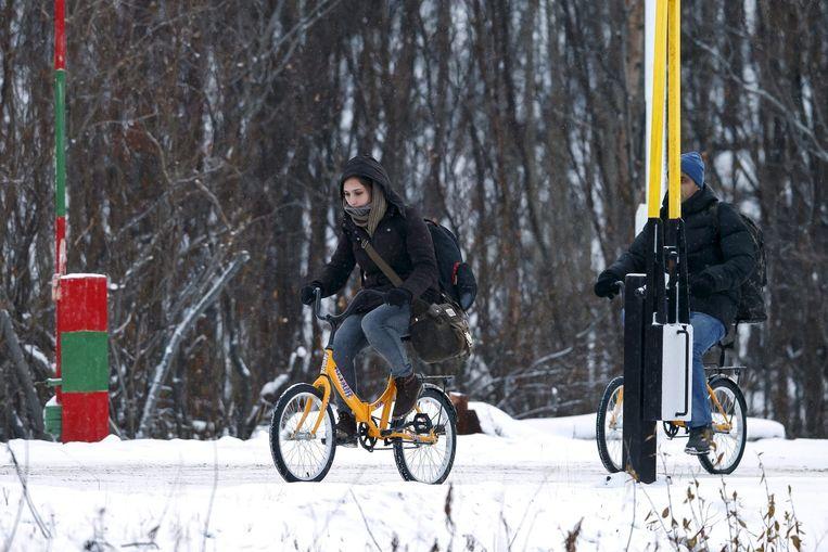 Vluchtelingen steken met de fiets de grens tussen Rusland en Noorwegen over. Beeld epa