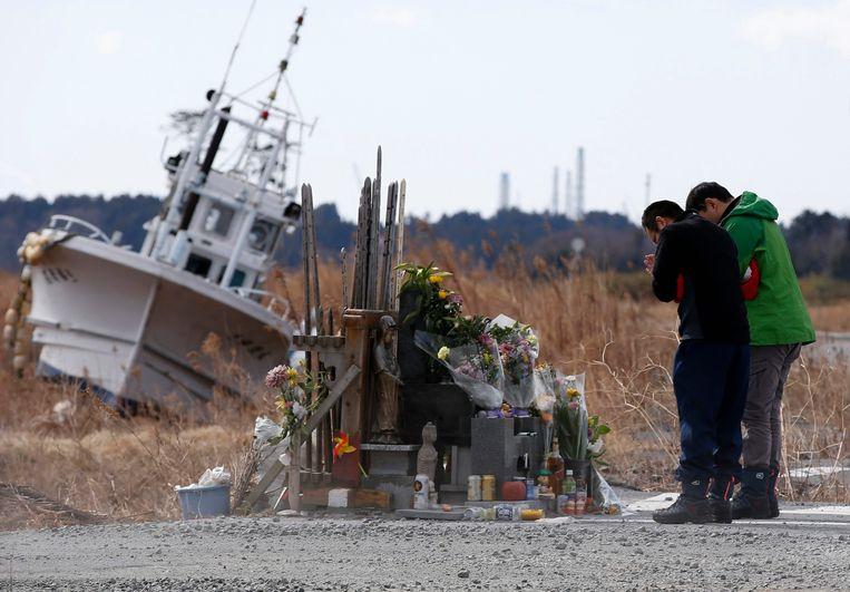 Mensen in gebed in 2011, na de tsunami die Fukushima trof.  Beeld REUTERS