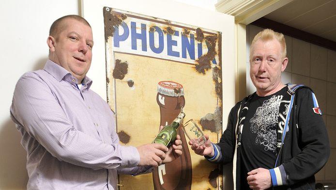 Titus Klijsen (links) en Jan van Hal bij de wc-deur van Klijsen met daarop oude Phoenixreclame.
