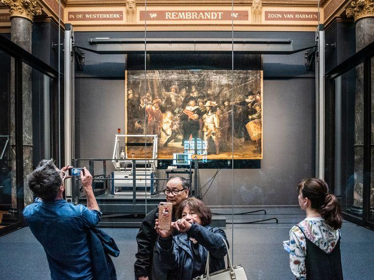 Bezoekers van het Rijksmuseum aanschouwen het beroemde schilderij 'vanachter het glas'. Beeld Simon Lenskens / de Volkskrant