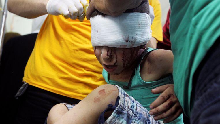 Dokters verzorgen een gewond Syrisch kind na gevechten in Idlib gisteren.