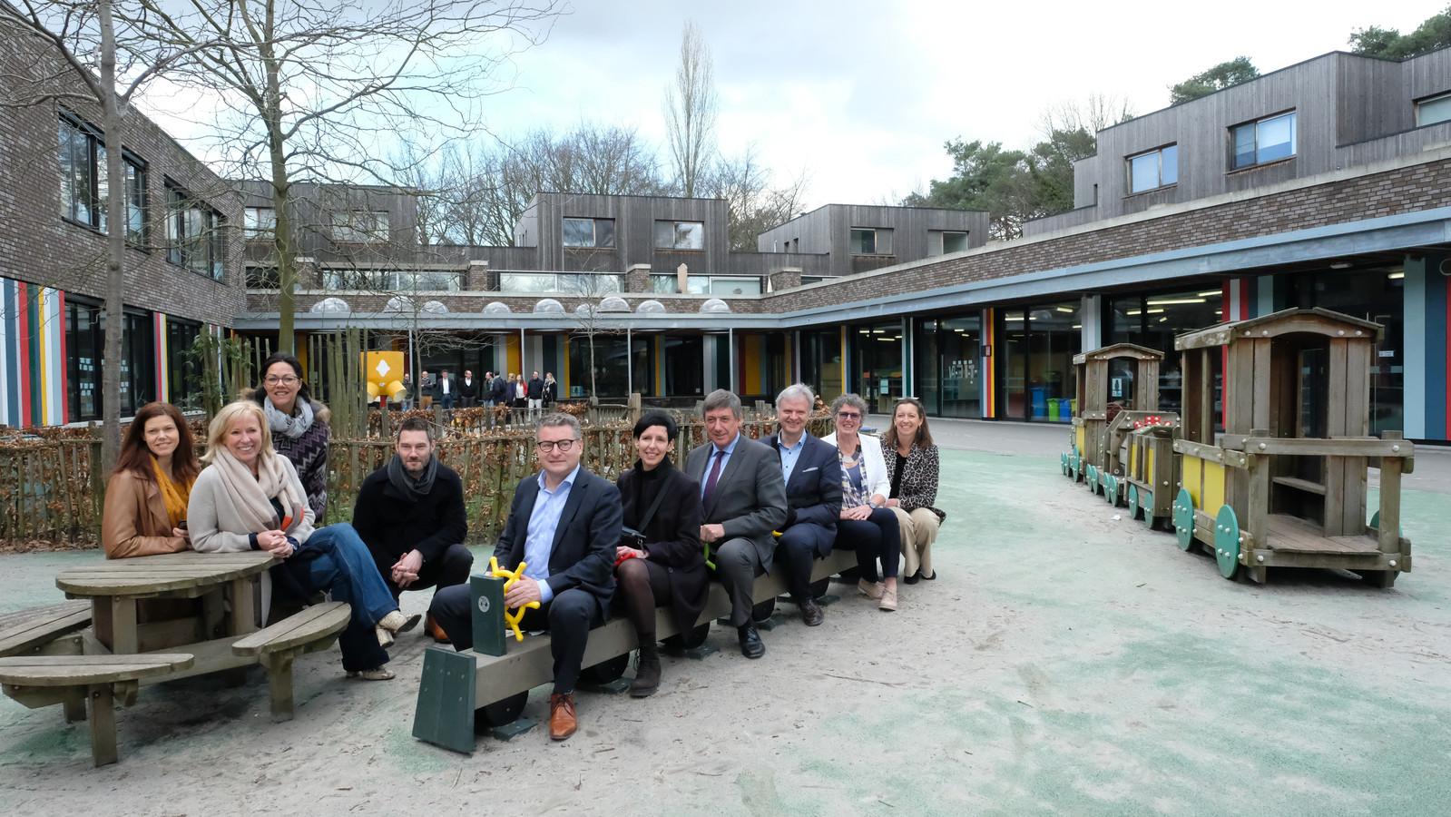 Koen Van Den Heuvel, burgemeester Jan Jambon en Dirk de Kort op de speelplaats van de school in Mariaburg.