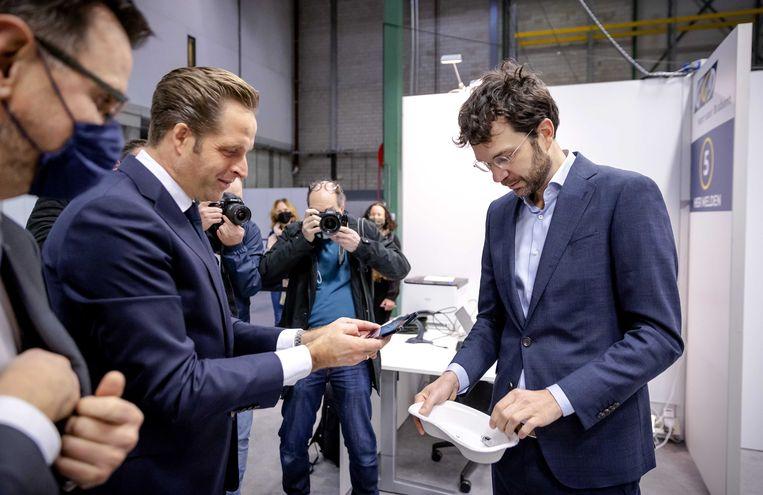 Jaap van Delden (r) bekijkt in het bijzijn van minister Hugo de Jonge en GGD-voorman Andre Rouvoet het ampul van het eerste vaccin.  Beeld ANP