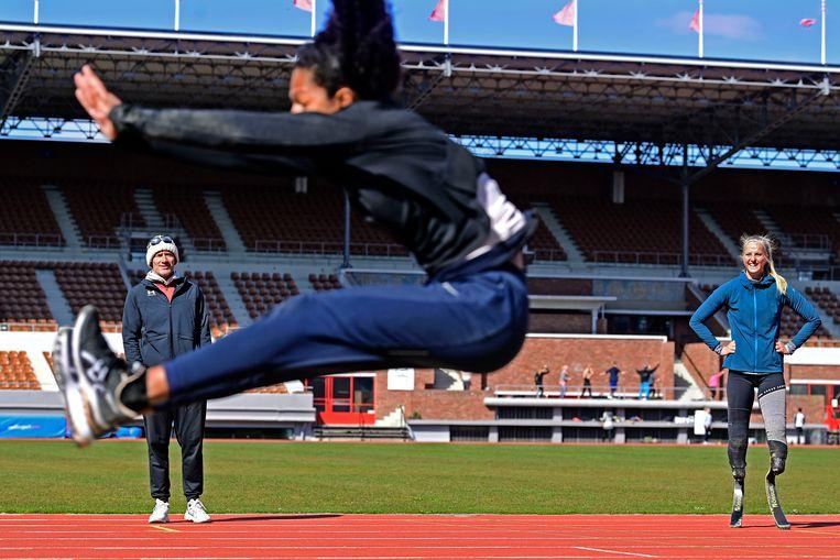Verspringster Fleur Jong en coach Guido Bonsen kijken tijdens een training van Team Para Atletiek  naar Tara Yoro.  Beeld Olaf Kraak