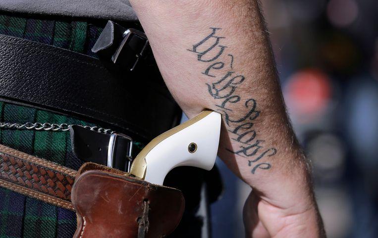 Een man draagt openlijk een pistool in Texas. Op zijn arm staan de eerste woorden van de Amerikaanse grondwet: 'We the people', 'wij, het volk'. Beeld AP