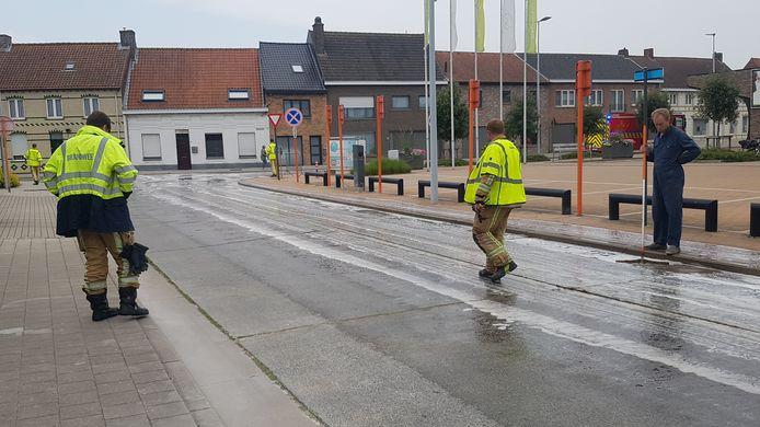 De brandweer spuit het wegdek schoon nadat een landbouwer zo'n 200 liter vloeibare mest verloor in Aartrijke. Ook de landbouwer helpt mee poetsen met een trekker.