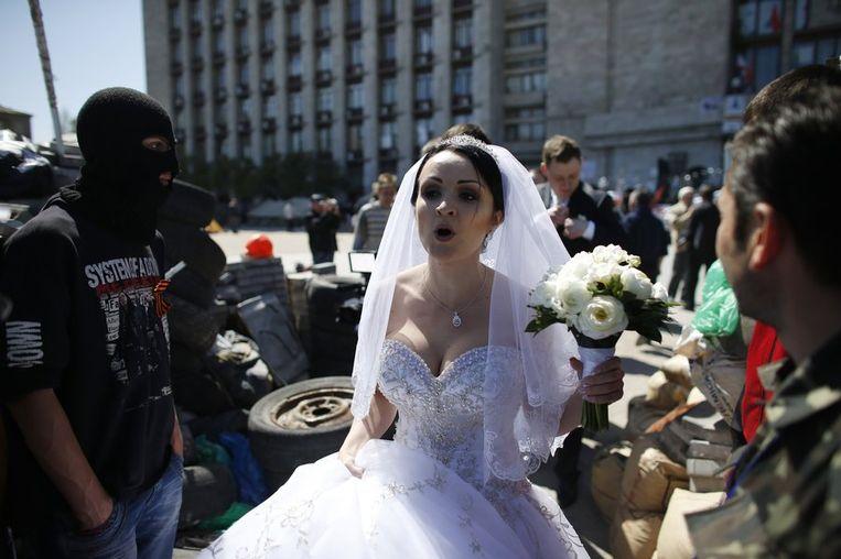 Een bruid passeert pro-Russische separatisten bij een barricade voor het bezette overheidsgebouw in Donetsk. Beeld reuters