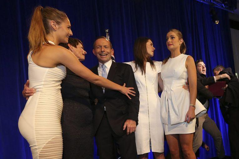 Curieus moment tijdens de bijeenkomst waarbij Tony Abbott de overwinning claimt: een indringer die met Abbott en diens gezin het podium beklom, wordt afgevoerd door veiligheidsagenten. Beeld afp