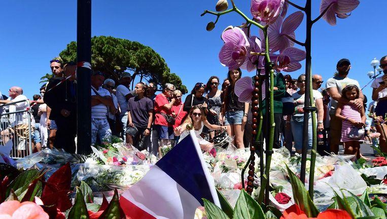 Inwoners en toeristen leggen bloemen neer op de boulevard waar donderdag zeker 84 mensen zijn omgekomen. Beeld afp