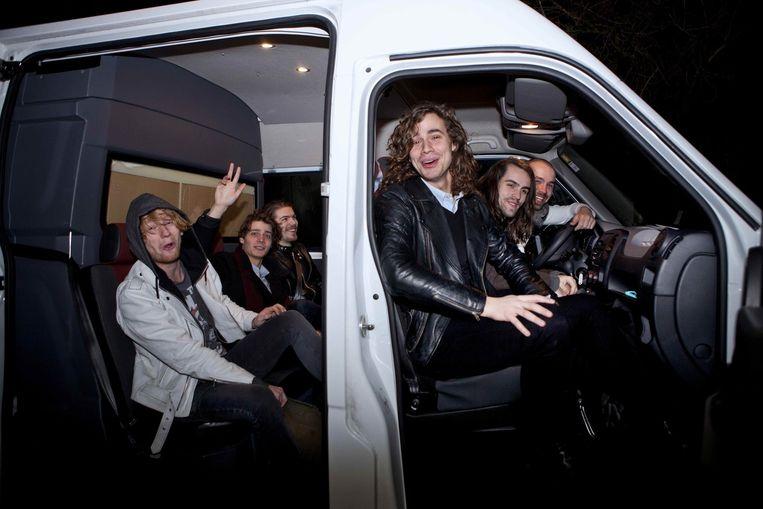 Lucas Hamming (derde van rechts) en zijn muzikanten dinsdagochtend om zes uur bij het vertrek naar Parijs: 'We hebben voor het eerst een echte bus gehuurd.' Beeld Mark van der Zouw