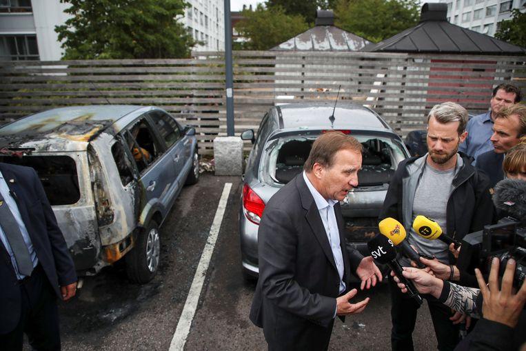 De Zweedse premier Stefan Löfven praat met journalisten voor een paar kapotte auto's  in Gotenburg. Beeld REUTERS