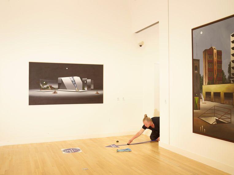 Een medewerker van Museum de Fundatie plakt bewegwijzering op de vloer. Afgelopen zomer werd het museum  gereed gemaakt voor heropening na de eerste lockdown.  Beeld Henk Wildschut