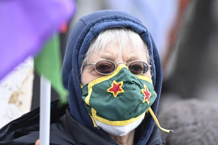 Een vrouw draagt tijdens een pro-Koerdische demonstratie in Berlijn een mondkapje met daarop het PKK-logo. Beeld AFP