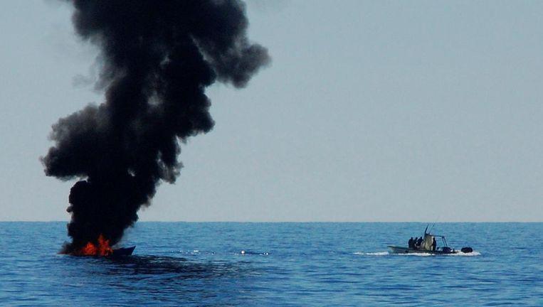 Een migrantenboot is in brand gestoken door de Libische kustwacht nadat de opvarenden zijn gered door ngo-schepen 20 mijl uit de kust van West-Libië, 18 mei. Beeld reuters