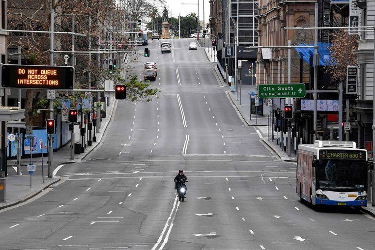 Een zo goed als lege straat in Sydney. Beeld AFP