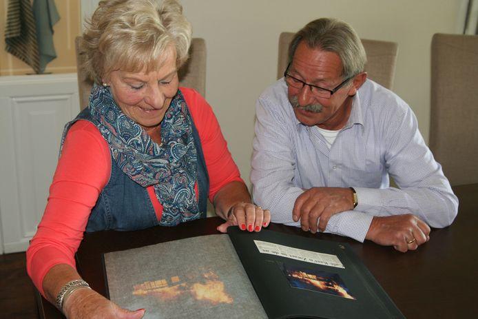 De vorige eigenaren Henk en Marietje Olde Riekerink bekijken het boek met vele foto's en krantenknipsels na de allesverwoestende brand bij Keet'n Zwart in 1989.