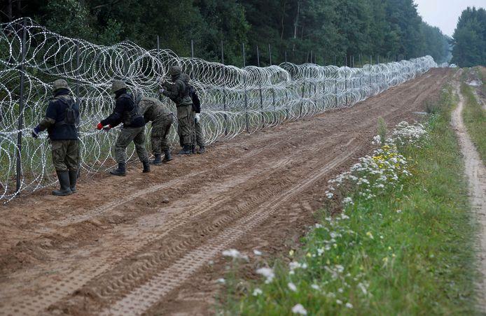 Des soldats polonais construisent une clôture à la frontière entre la Pologne et le Bélarus près du village de Nomiki, en Pologne, le 26 août 2021.