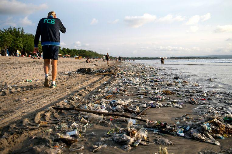 epa06391135 People walk next to piles of plastic debris brought in by strong waves on Kuta beach, Bali's best-known tourist destination, Indonesia, 15 December 2017.  EPA/MADE NAGI Beeld EPA