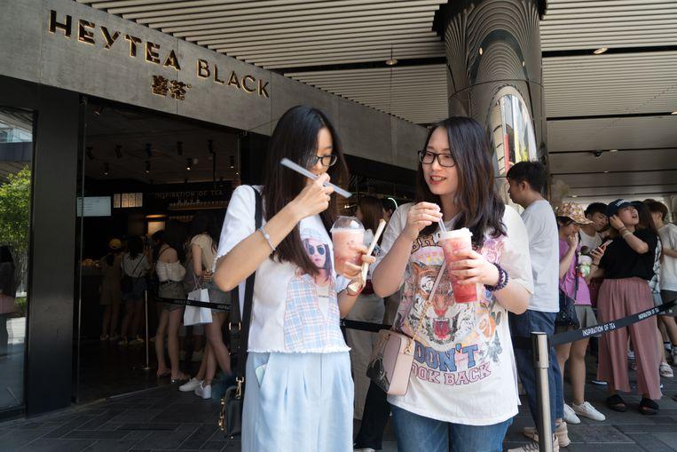 Lange rij voor de Heytea in Sanlitun area in Beijing. Buiten staat een rij, binnen wachten mensen met een bonnetje op hun (fruit) thee. Zhou (links) en Zhang hebben hun slag al geslagen.  Beeld Ruben Lundgren