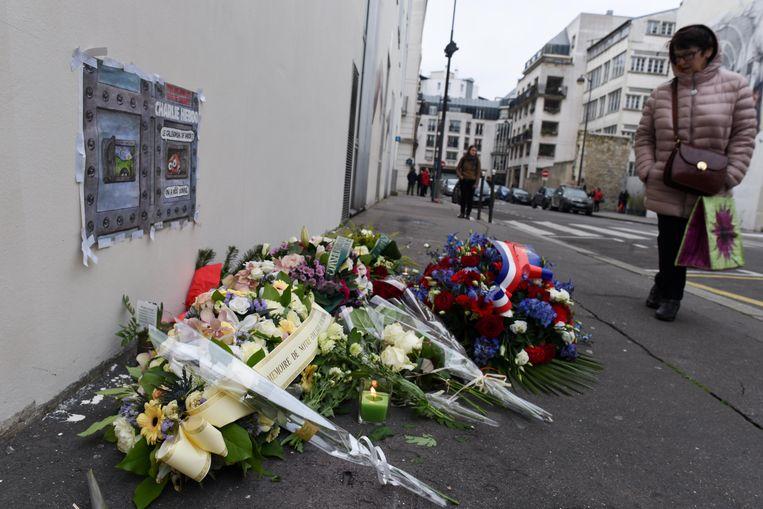 Parijzenaars herdenken de aanslag op Charlie Hebdo, op 7 januari 2015, aan het voormalige kantoorgebouw van de satirische krant. Beeld Photo News