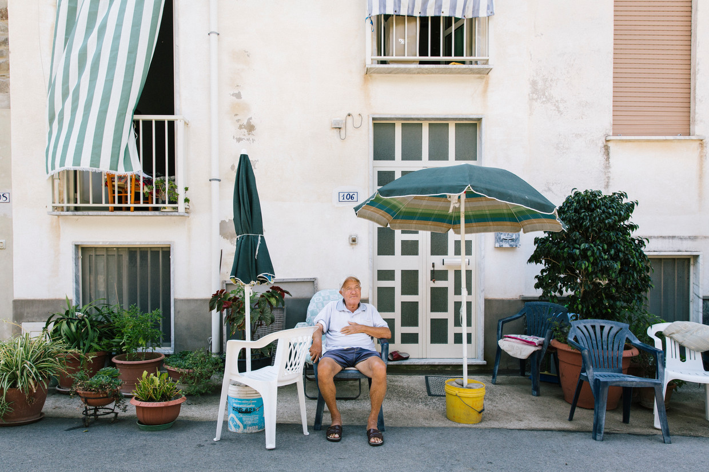 Een inwoner van Acciaroli (81) zit voor zijn huis.