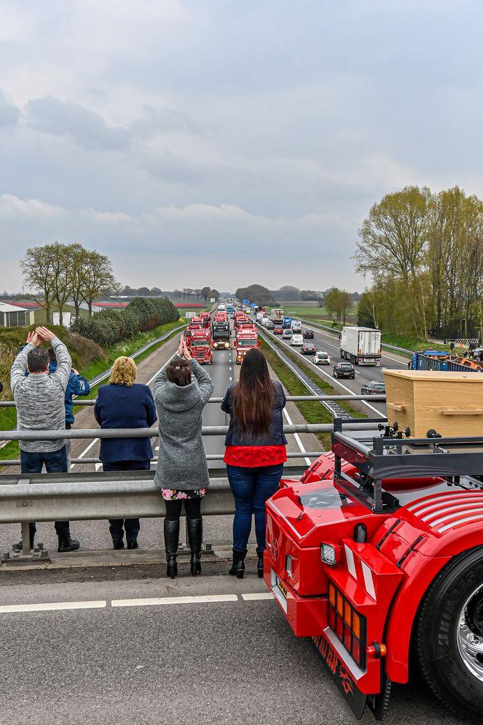 De rouwstoet op de A58 nadert het viaduct bij Heerle met daarop de truck met de kist.