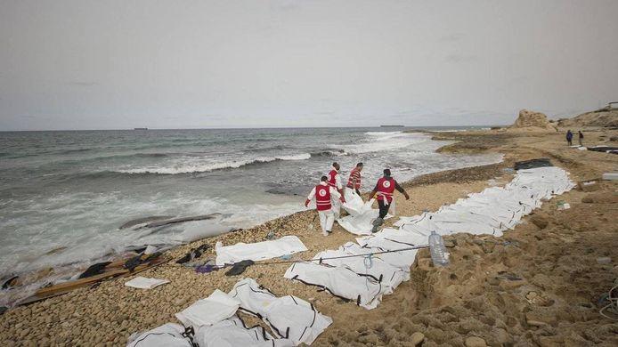 Medewerkers van het Rode Kruis tussen de dode lichamen van aangespoelde migranten in Libië.