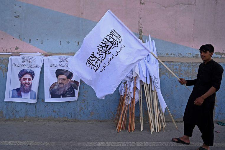 Op straat in Kabul worden Talibanvlaggen verkocht. Op de rechter poster staat Abdul Ghani Baradar.  Beeld AFP