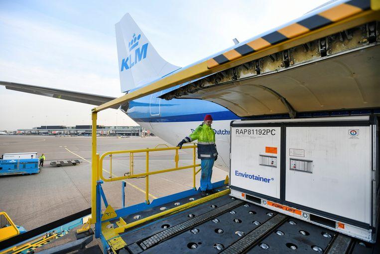 Koelboxen worden vervoerd via Schiphol om klaar te zijn voor de vaccinatiecampagne.  Beeld REUTERS