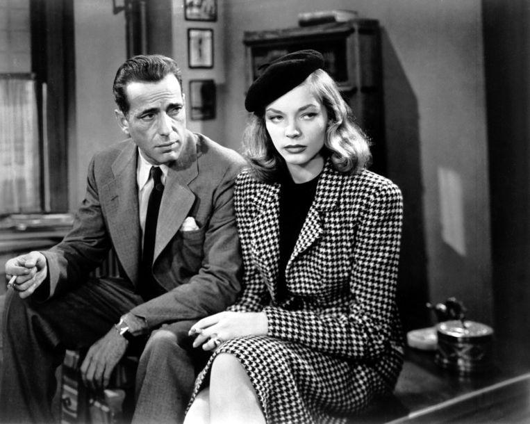 Acteur Humphrey Bogart (1889 - 1957) in zijn rol als Philip Marlowe en Lauren Bacall als zijn tegenspeelster Vivian Rutledge in de film 'The Big Sleep' uit 1946. Beeld getty