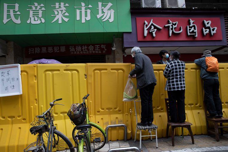 Inwoners halen boodschappen bij verkopers in een afgesloten wijk van Wuhan, in april 2020. Beeld AP