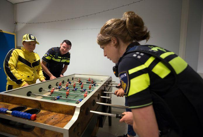 Bram Naberhuis en de Didamse wijkagente Marieke Brugman spelen een potje tafelvoetbal in jeugdhonk D-vision in Didam.