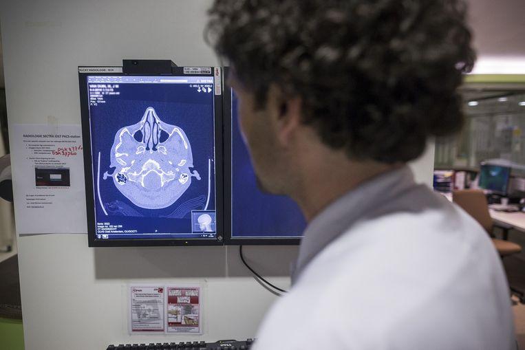 Arts Michiel Gorzeman bekijkt de foto van het gebroken jukbeen. Beeld Rink Hof