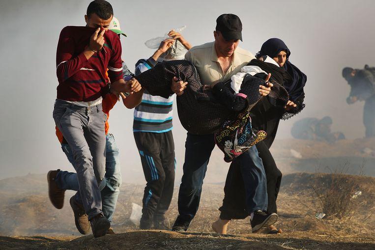 Palestijnse demonstranten in Gaza brengen een gewonde vrouw weg in een wolk van traangas. Beeld Getty Images