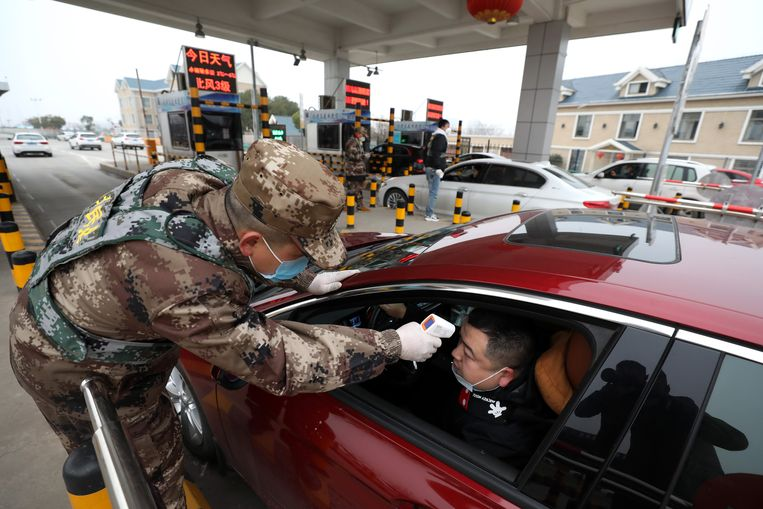 De temperatuur van een bestuurder in Wuhan wordt gemeten.