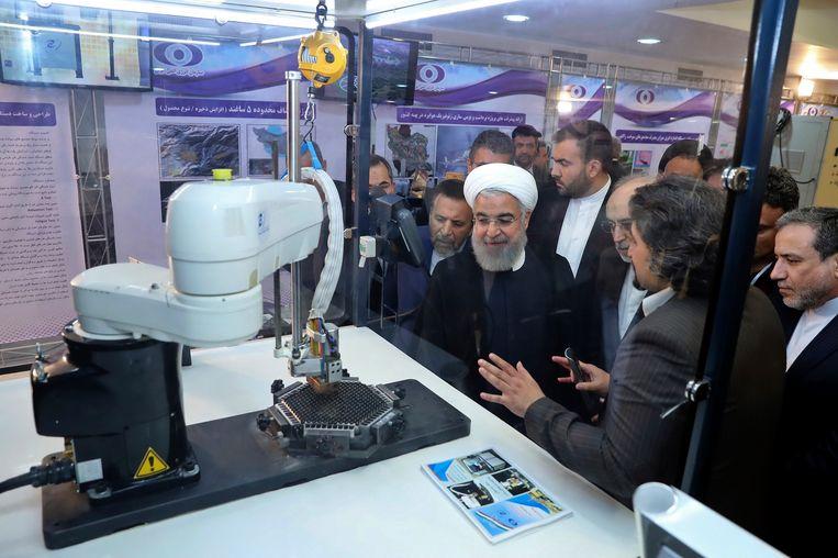 De Iraanse president Hassan Rouhani luistert naar uitleg tijdens de 'National Nuclear Day'.  Beeld AP